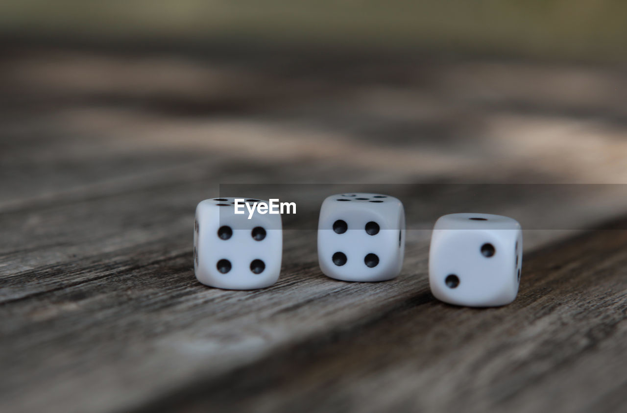 dice, leisure games, relaxation, table, leisure activity, arts culture and entertainment, gambling, wood - material, luck, opportunity, still life, close-up, selective focus, indoors, cube shape, no people, high angle view, spotted, geometric shape, white color, game of chance, surface level