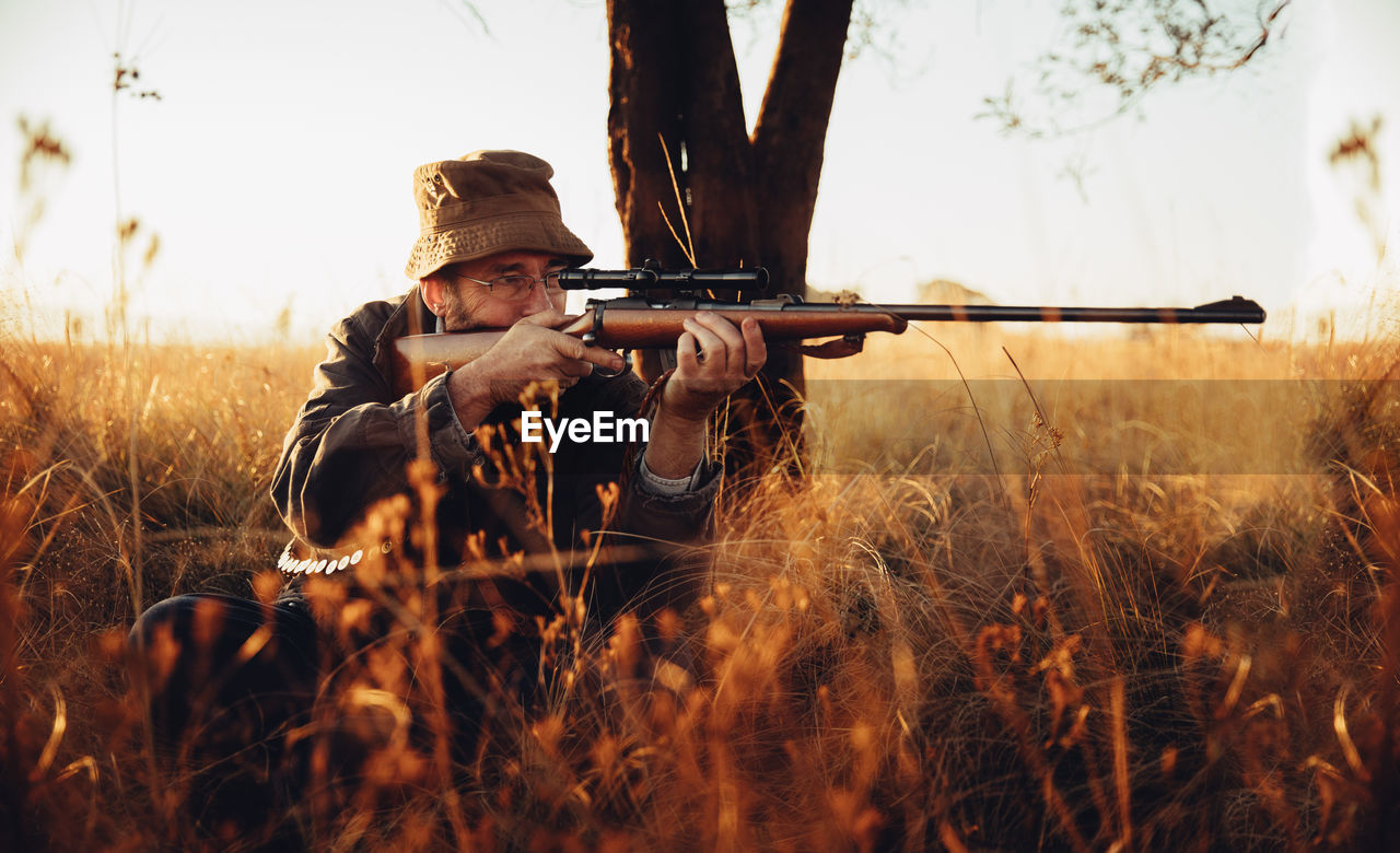 Man Aiming Rifle By Tree Trunk On Field