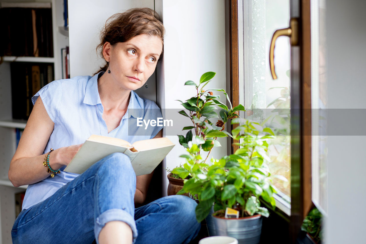 Thoughtful woman with book looking through window at home