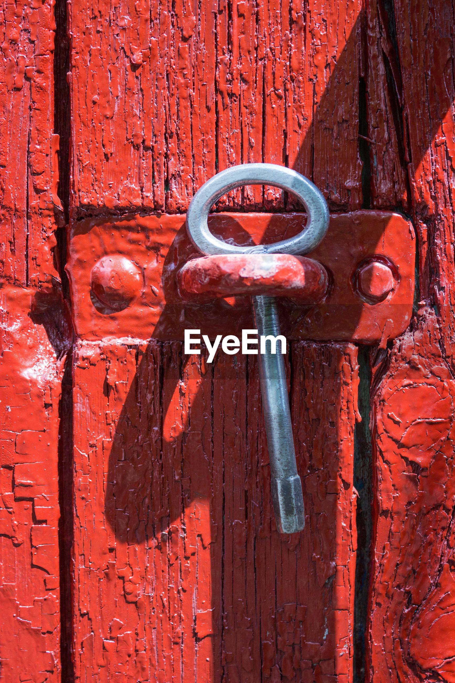 Close-up of key in red door