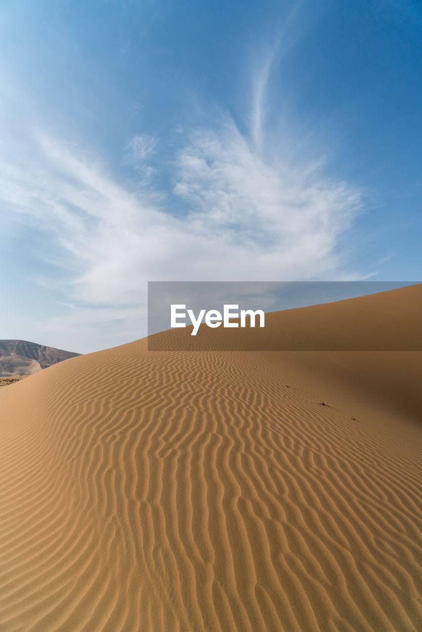 View Of Badain Jaran Desert Against Cloudy Sky