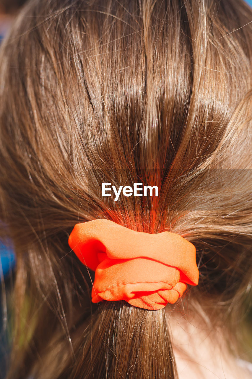Rear view of woman with orange hair elastic