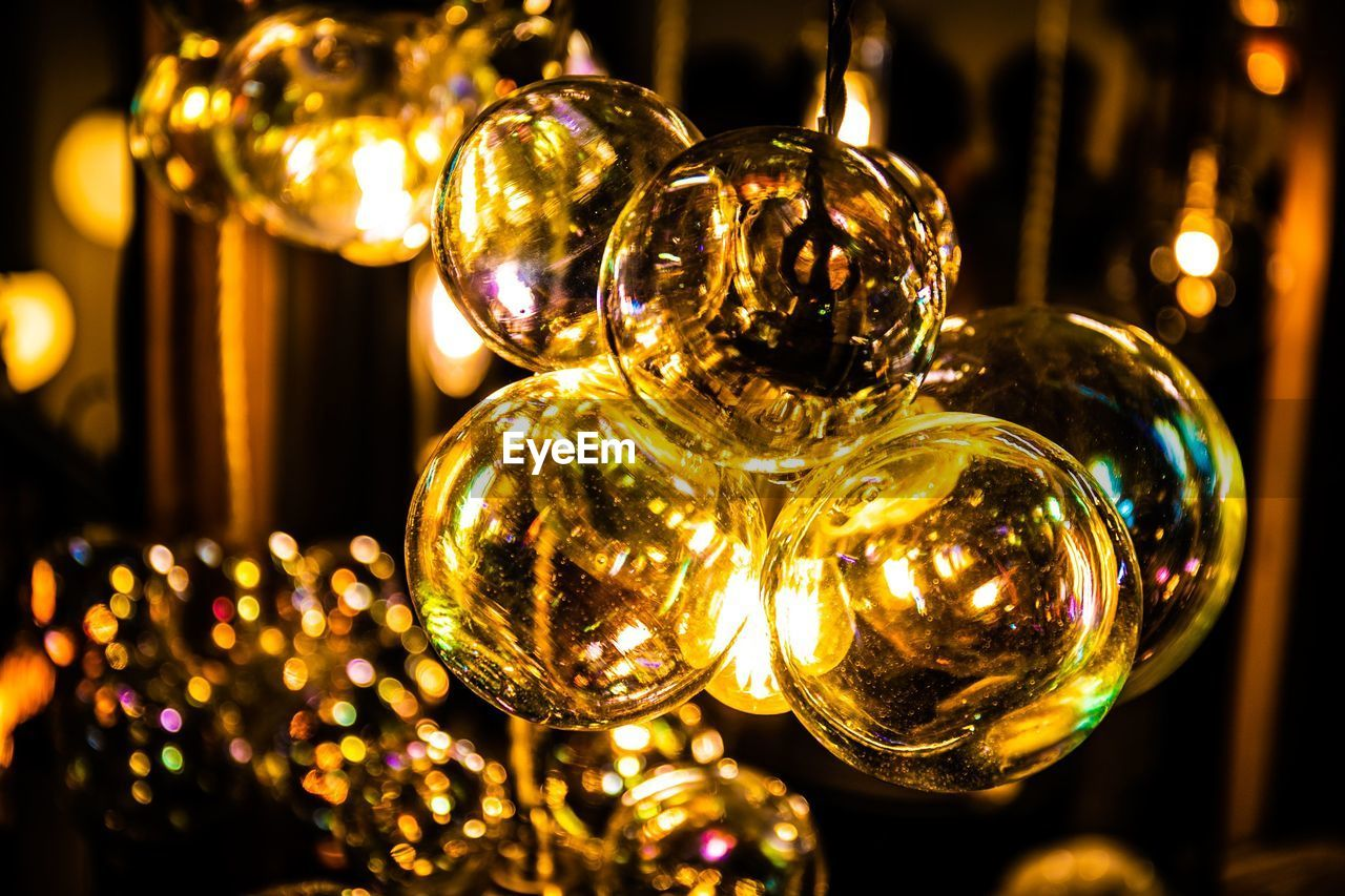 illuminated, decoration, focus on foreground, sphere, close-up, holiday, shiny, hanging, no people, reflection, christmas, christmas decoration, glass - material, indoors, celebration, christmas ornament, night, lighting equipment, selective focus, light, silver colored