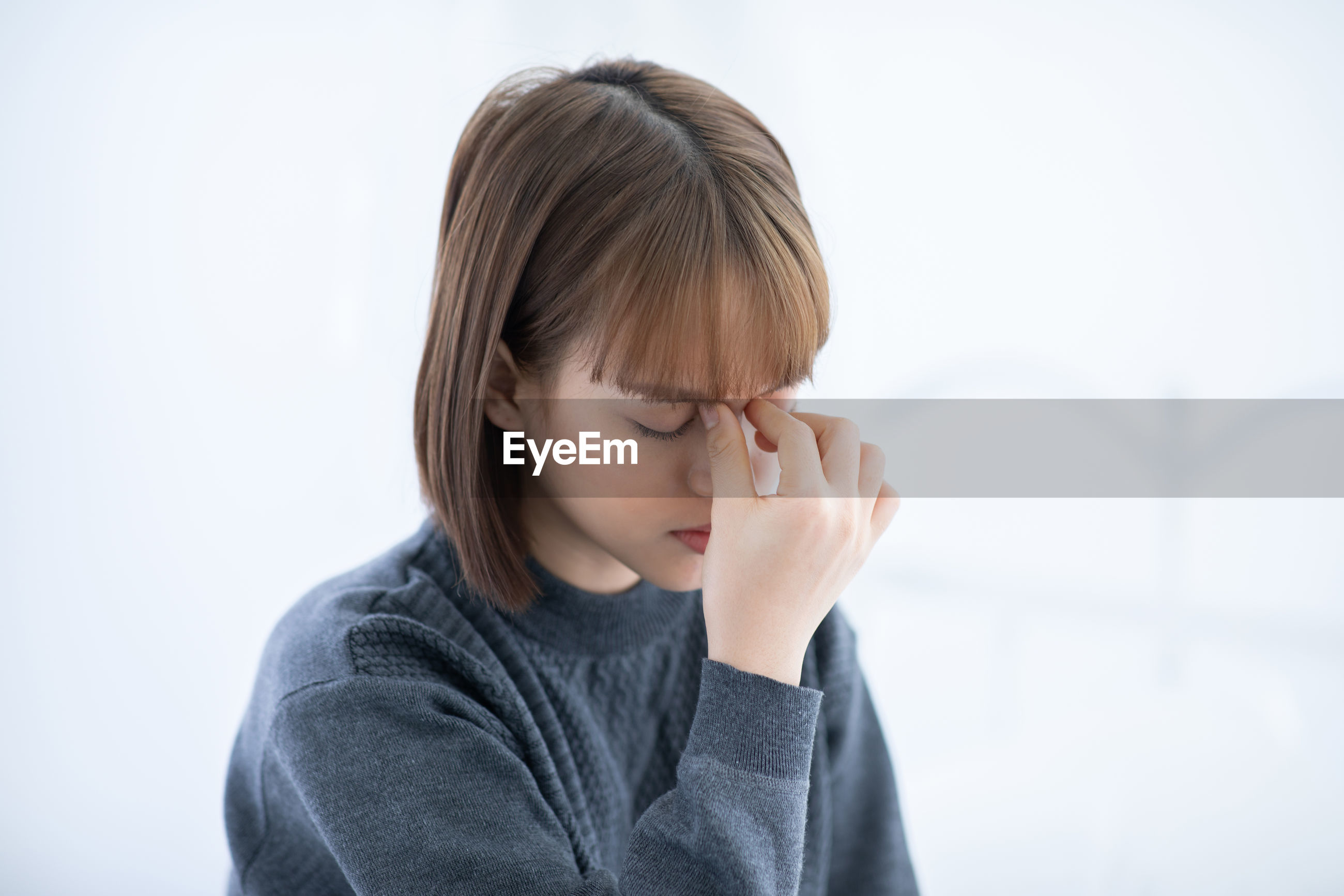 Young woman suffering from headache at home