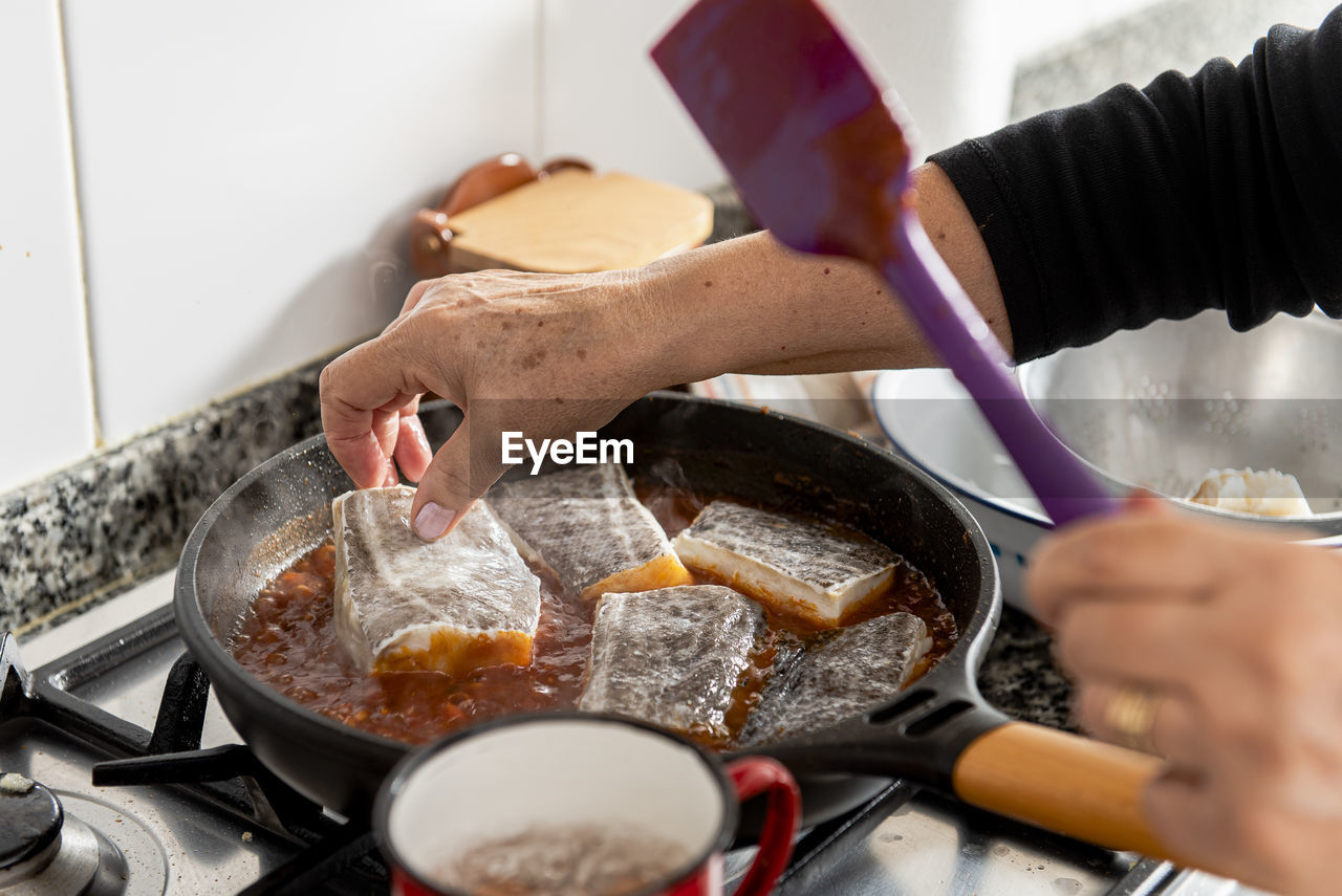 MIDSECTION OF PERSON HAVING FOOD IN KITCHEN