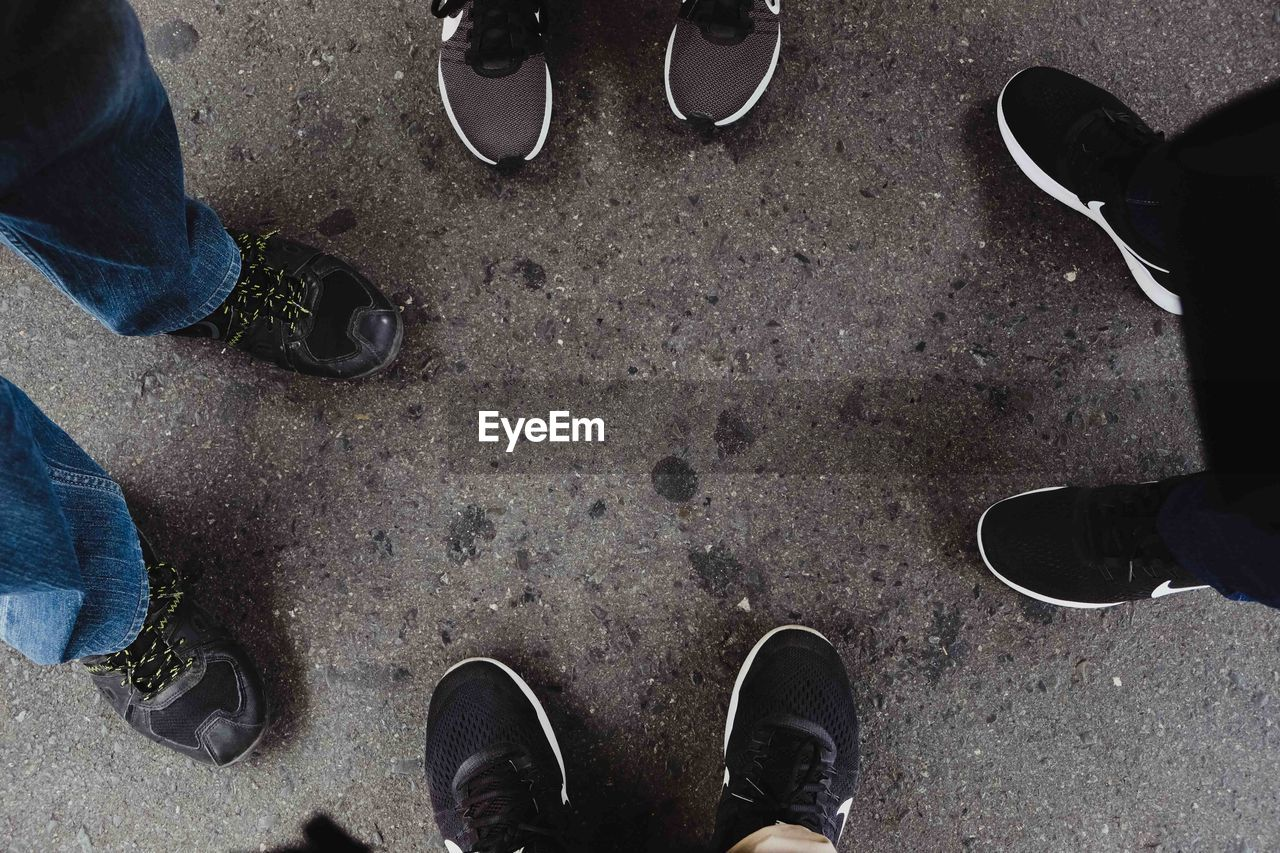 low section, human leg, shoe, real people, human body part, body part, high angle view, standing, men, personal perspective, lifestyles, directly above, people, day, friendship, leisure activity, togetherness, two people, city, outdoors, human foot, jeans