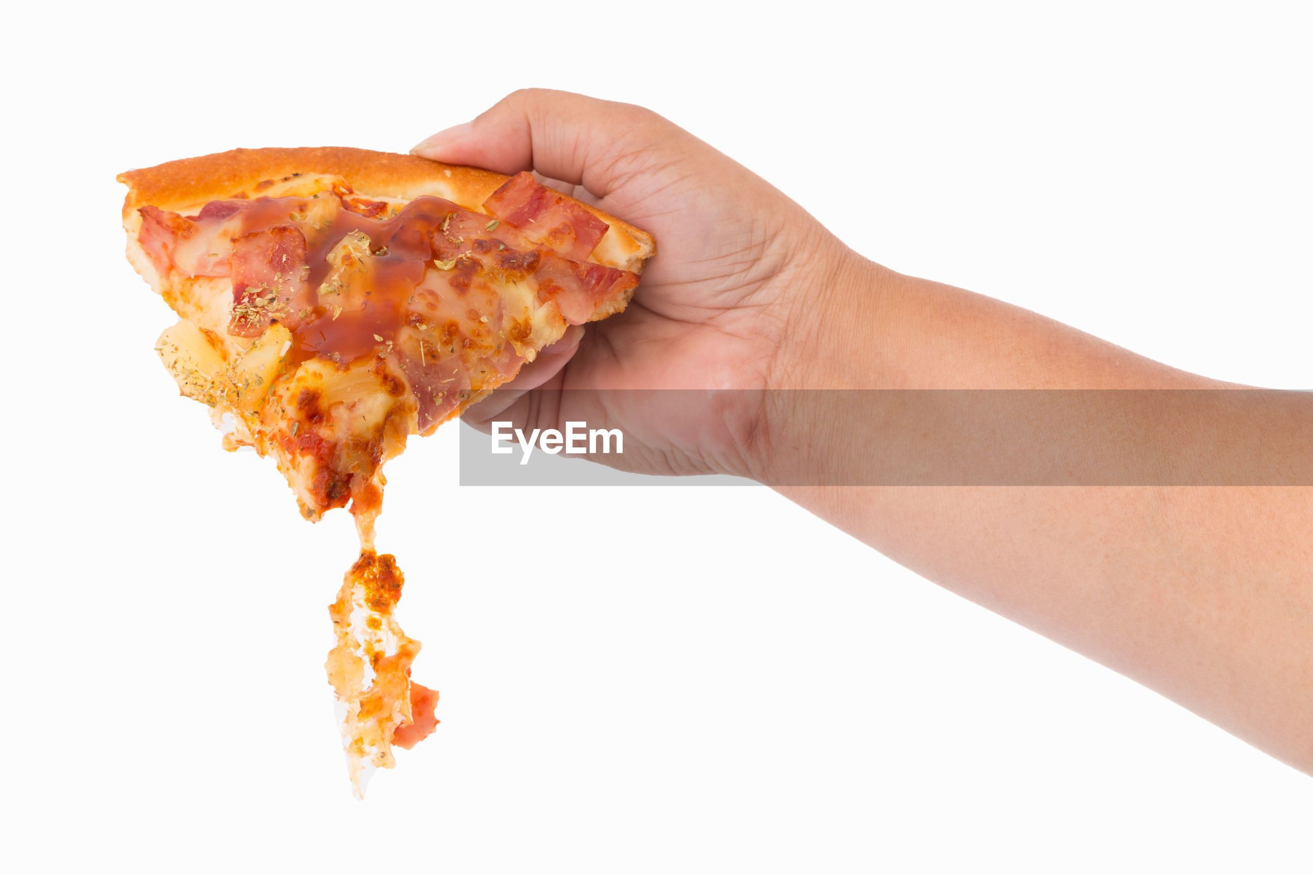 Close-up of hand holding pizza against white background