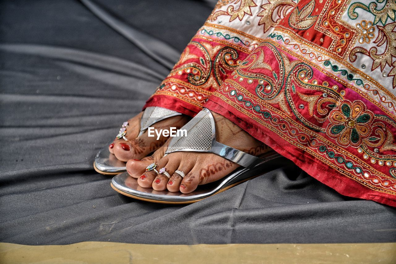 real people, one person, women, human body part, lifestyles, midsection, low section, adult, clothing, traditional clothing, body part, human hand, wedding, pattern, red, shoe, hand, close-up, human foot