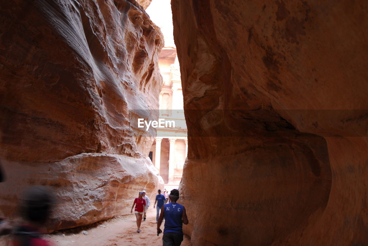 People walking amidst rock formations
