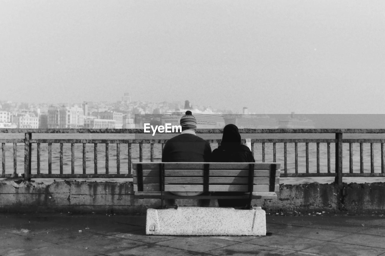 Rear View Of Couple Sitting On Bench By Sea Against Clear Sky