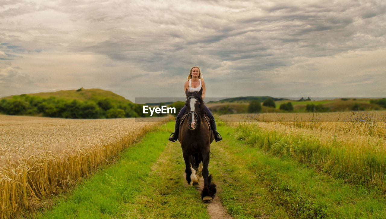Portrait of mid adult woman riding horse on grassy field against cloudy sky