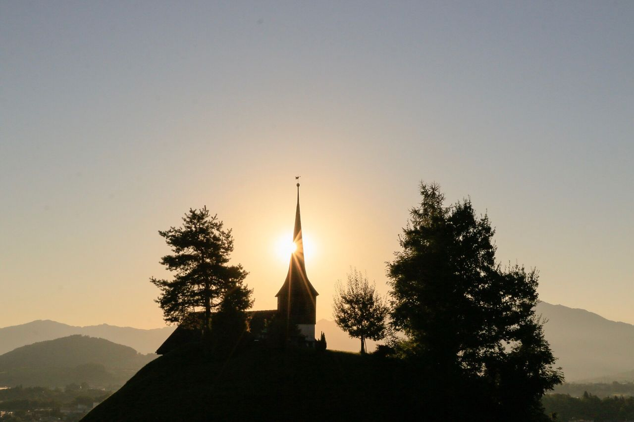 Church on hill against sky during sunset