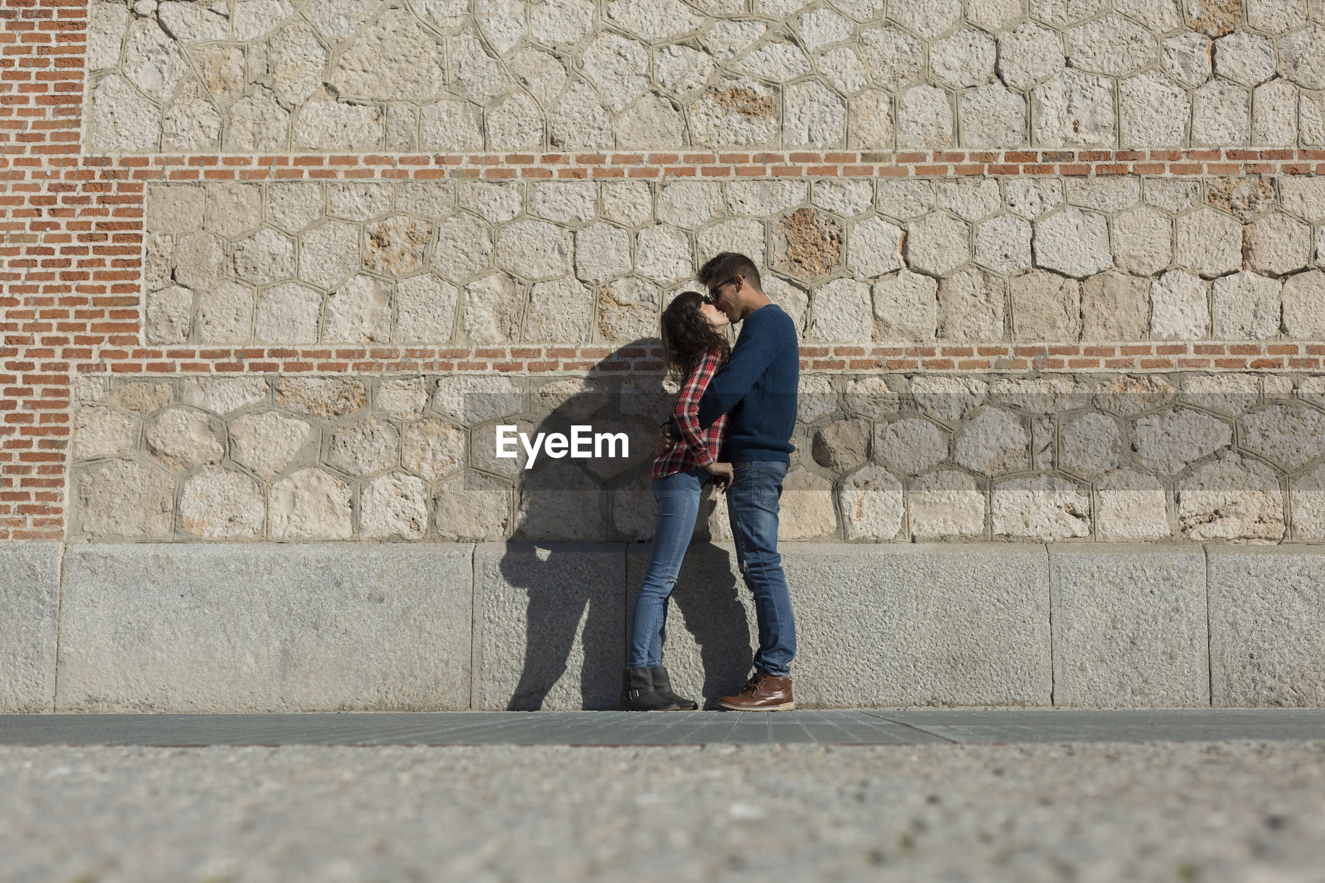 Side view of couple kissing against stone wall