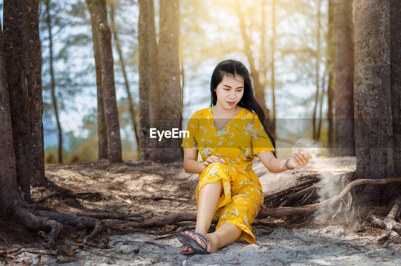 Smiling woman throwing sand while sitting on tree trunk