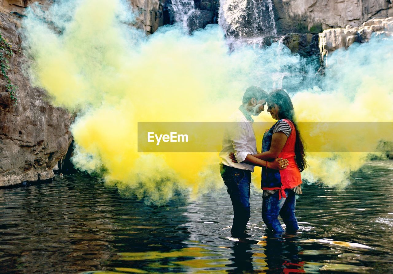Side View Of Young Couple Standing Amidst Yellow Smoke In Lake