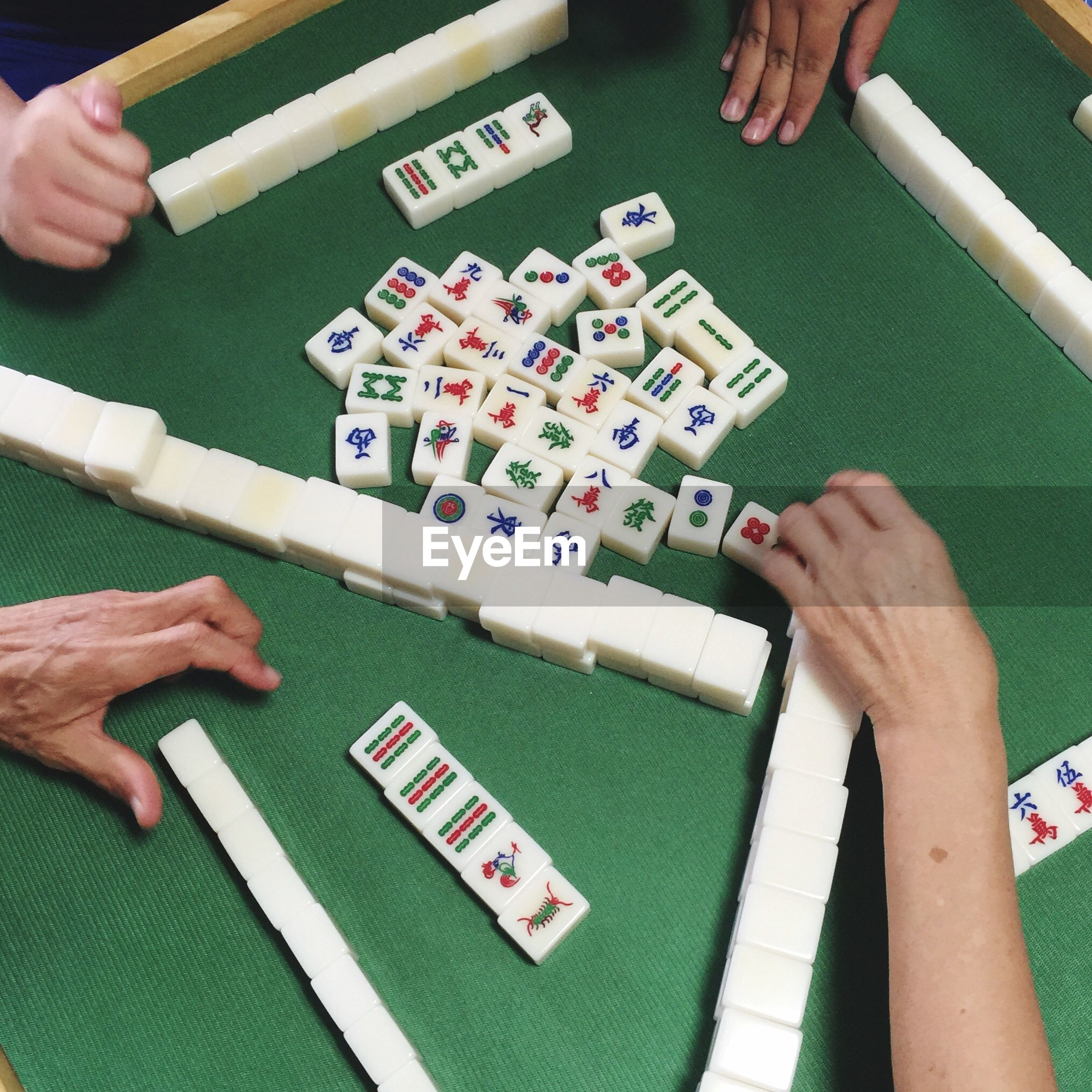 Cropped image of people playing mahjong on table