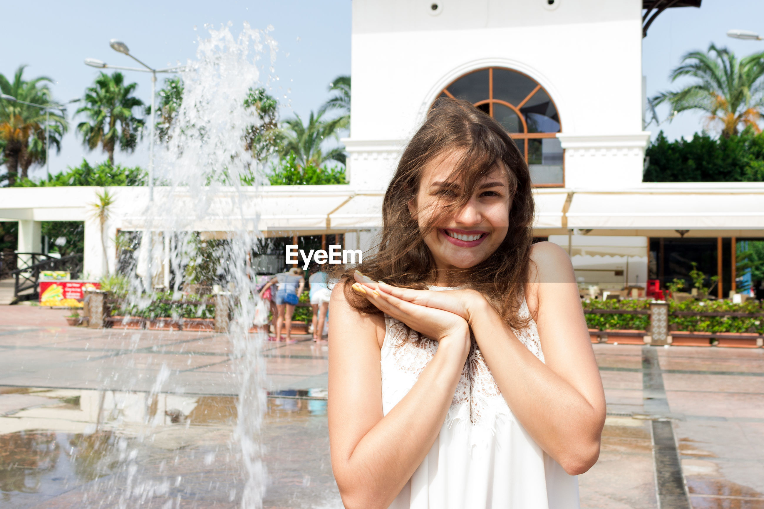 Portrait of smiling young woman standing at fountain