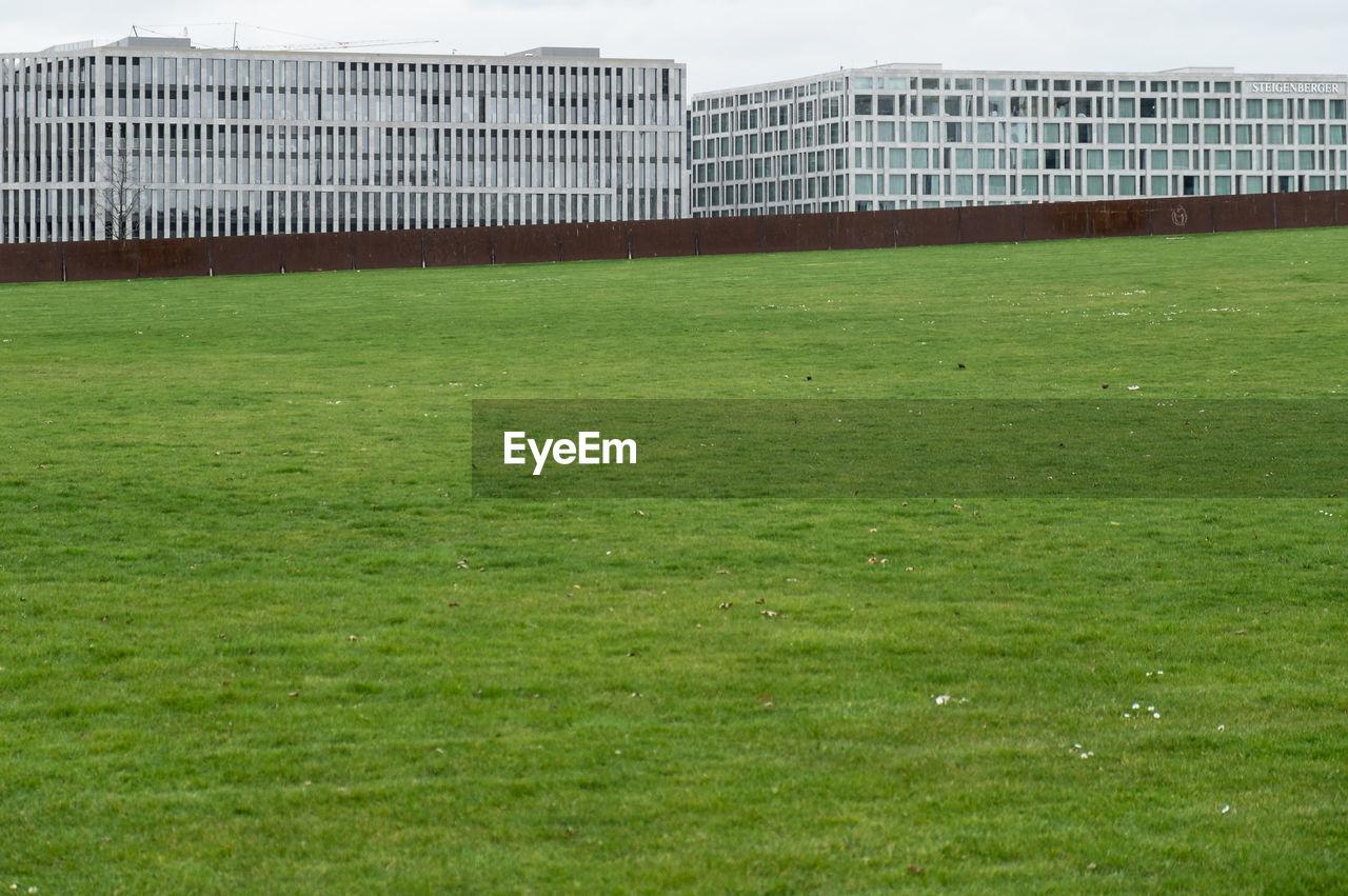 Modern Buildings By Grassy Field In City