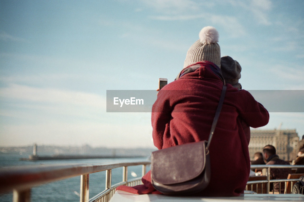 Rear view of mother and daughter looking at sea