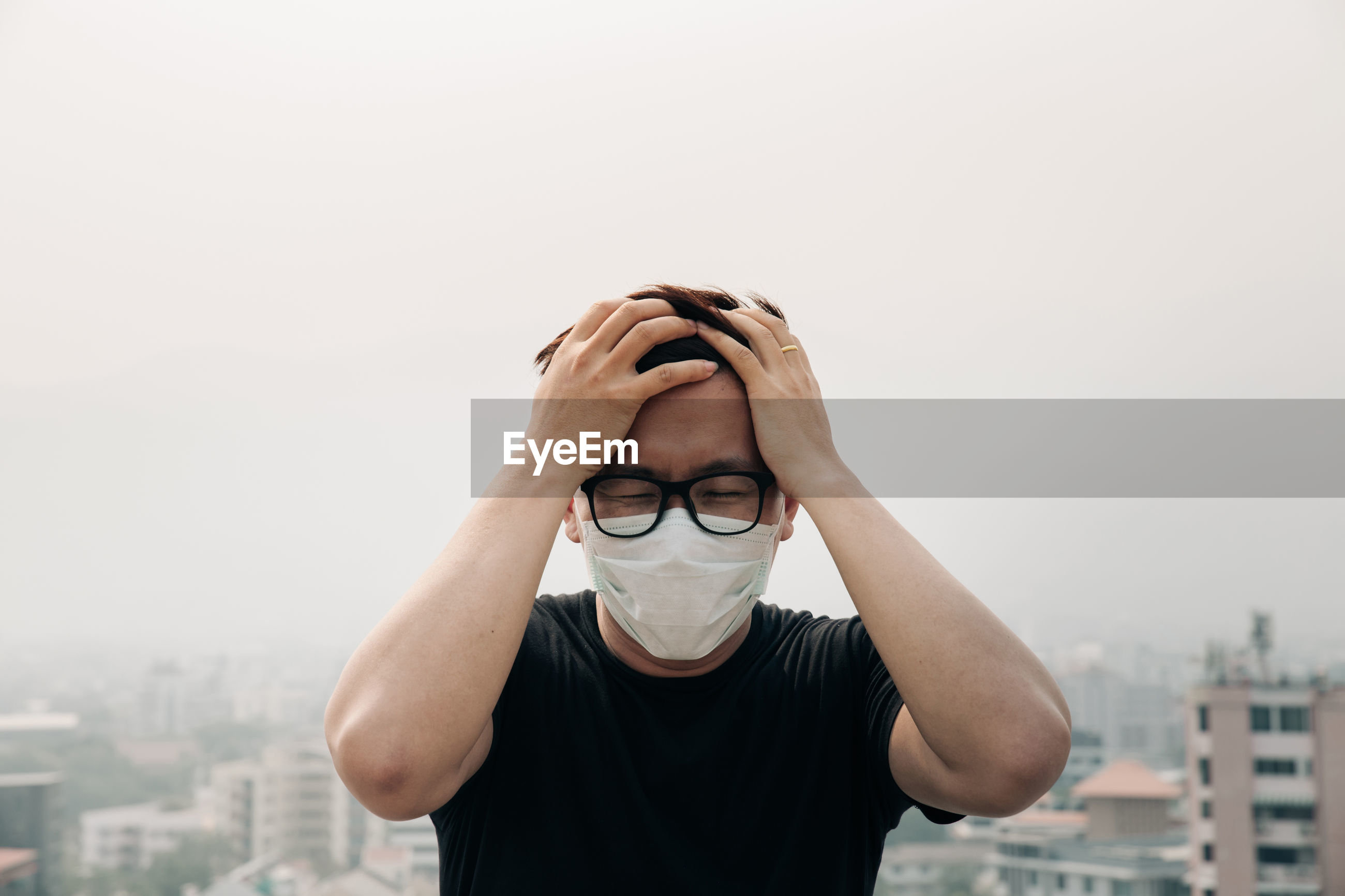 Worried man wearing surgical mask against buildings and sky