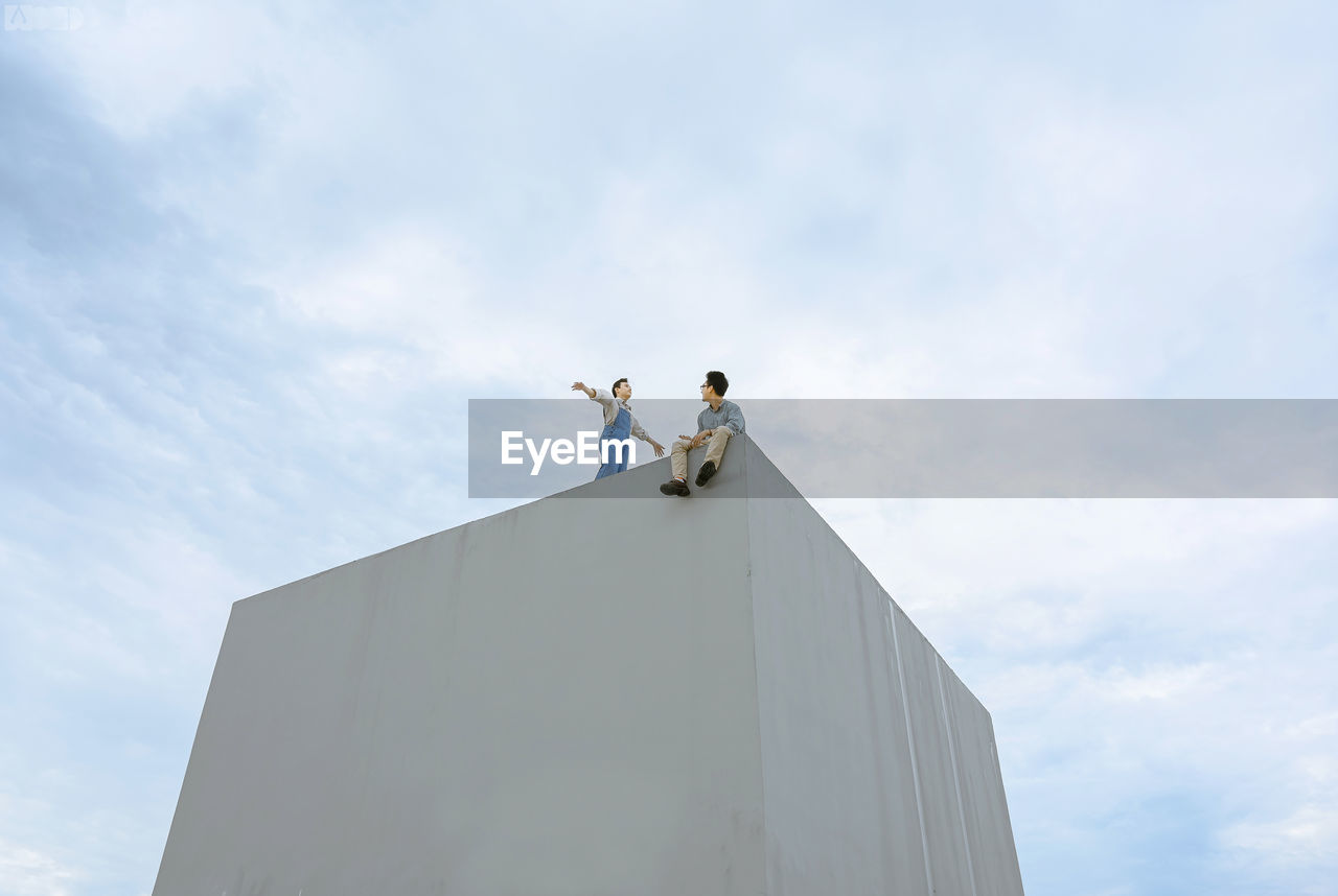 LOW ANGLE VIEW OF PEOPLE STANDING ON BUILDING