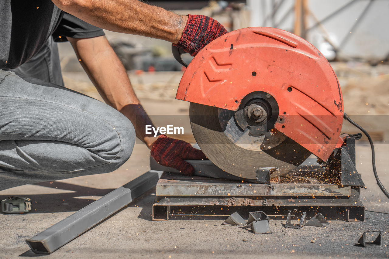 occupation, working, men, work tool, one person, real people, industry, day, cutting, metal, focus on foreground, circular saw, transportation, holding, land vehicle, mode of transportation, outdoors, workshop, mechanic, hand saw