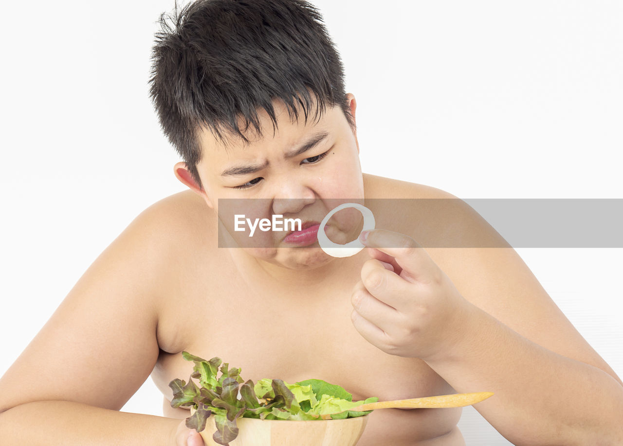 Shirtless boy crying while holding food in bowl against white background
