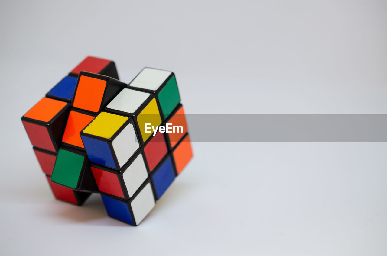 CLOSE-UP OF MULTI COLORED TOY ON WHITE BACKGROUND