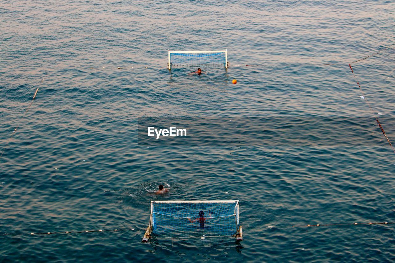 High angle view of people playing water polo at sea
