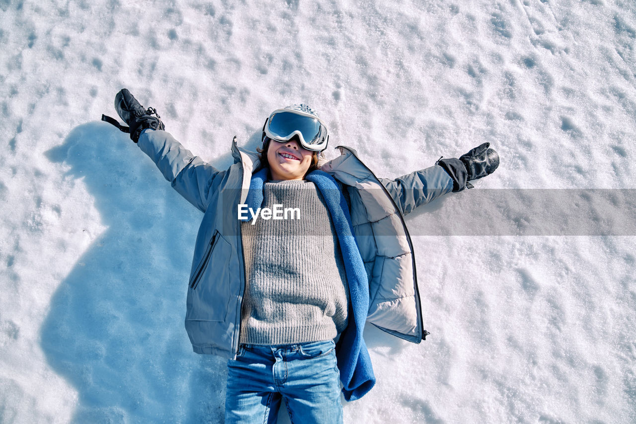 FULL LENGTH OF HAPPY MAN WITH ARMS RAISED ON SNOW