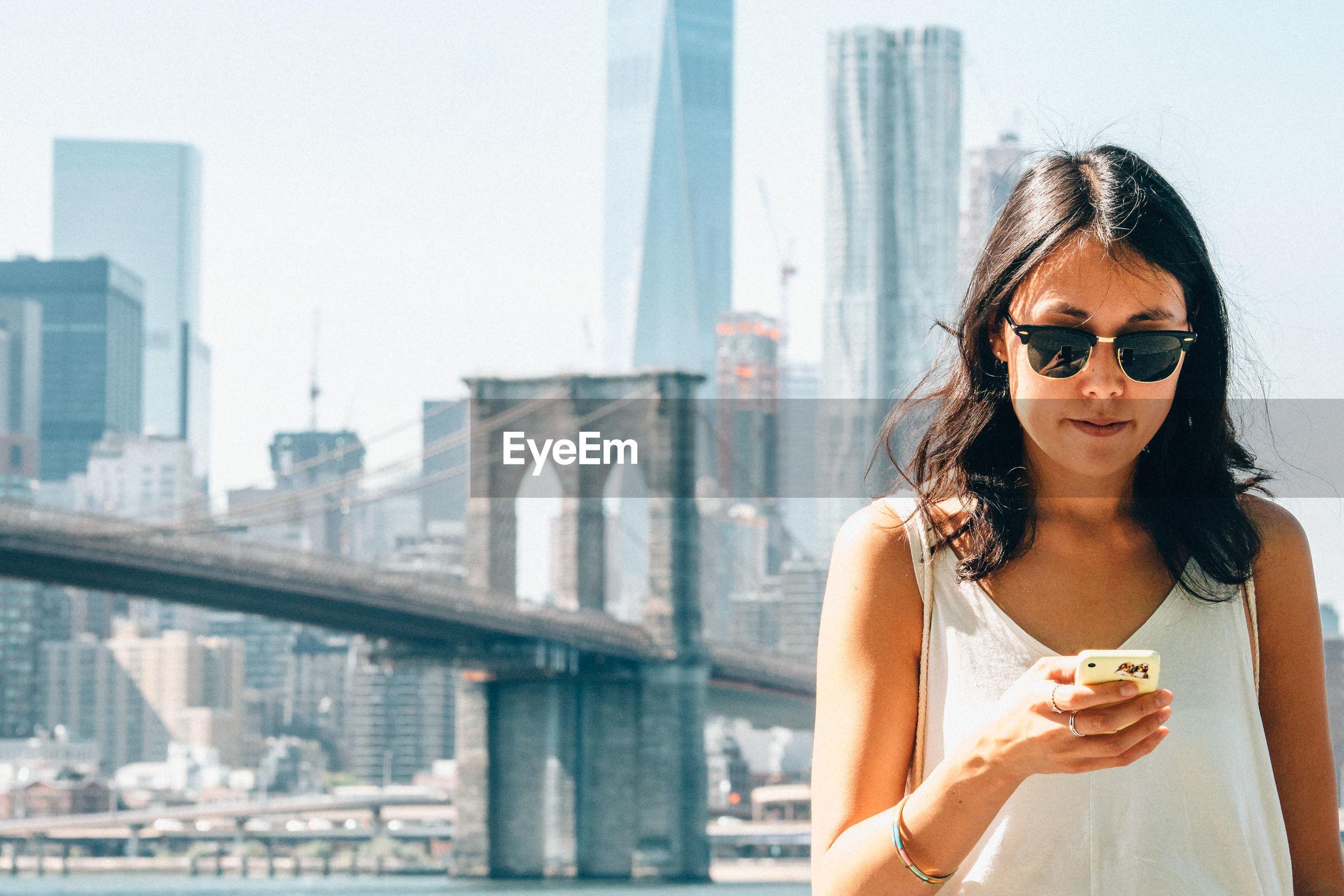 Young woman using smart phone against brooklyn bridge