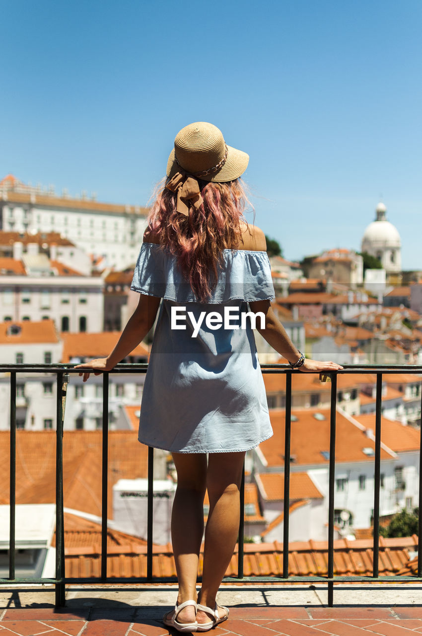 Rear View Of Young Woman Looking At Buildings While Standing By Railing In Balcony Against Clear Sky