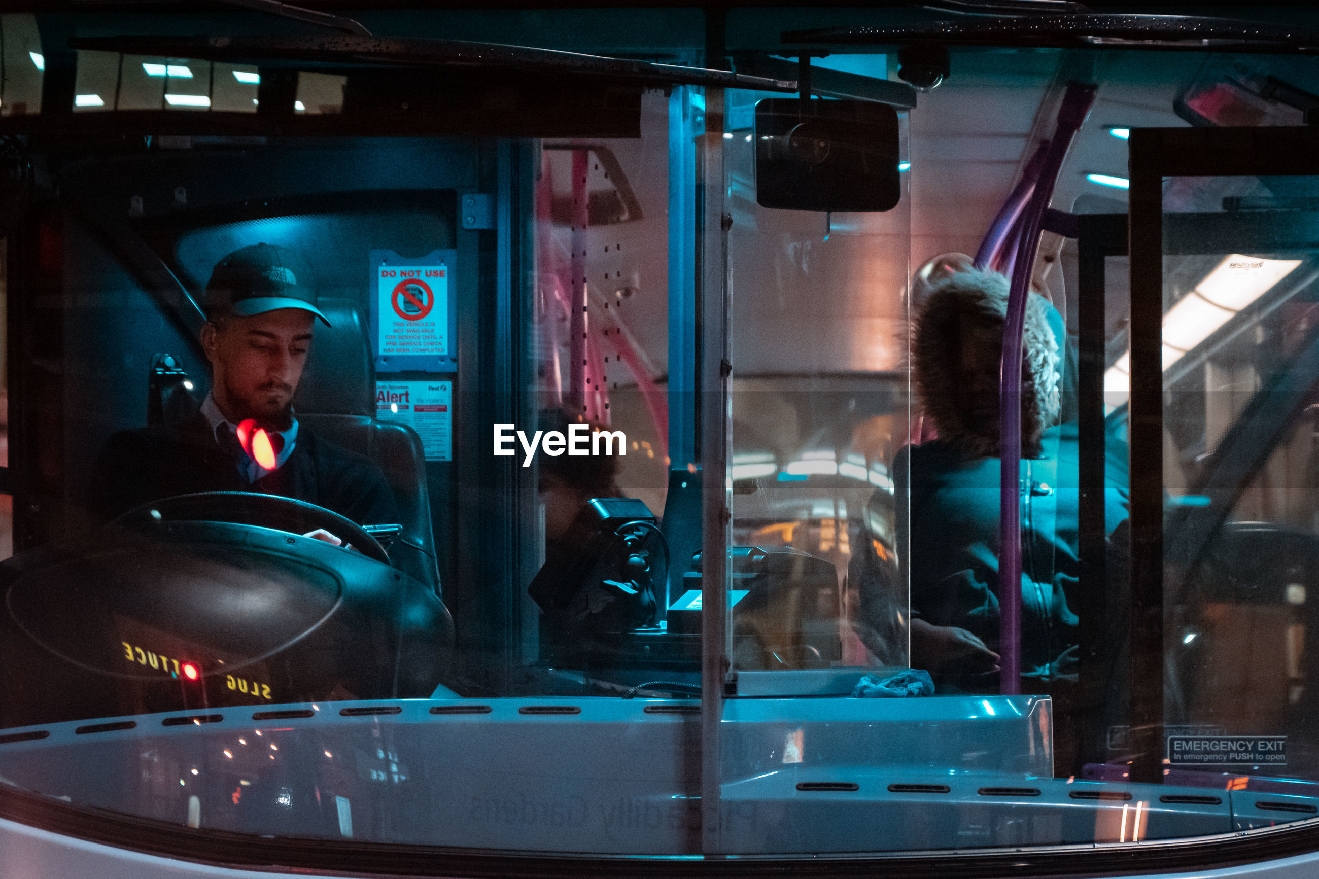 MAN LOOKING AT ILLUMINATED BUS WINDOW