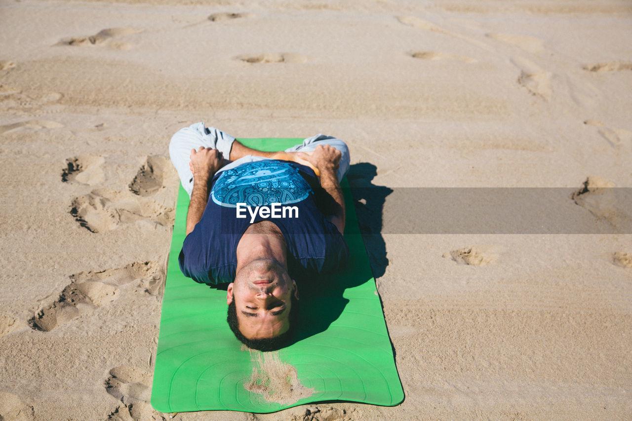 High Angle View Of Man Doing Yoga On Beach