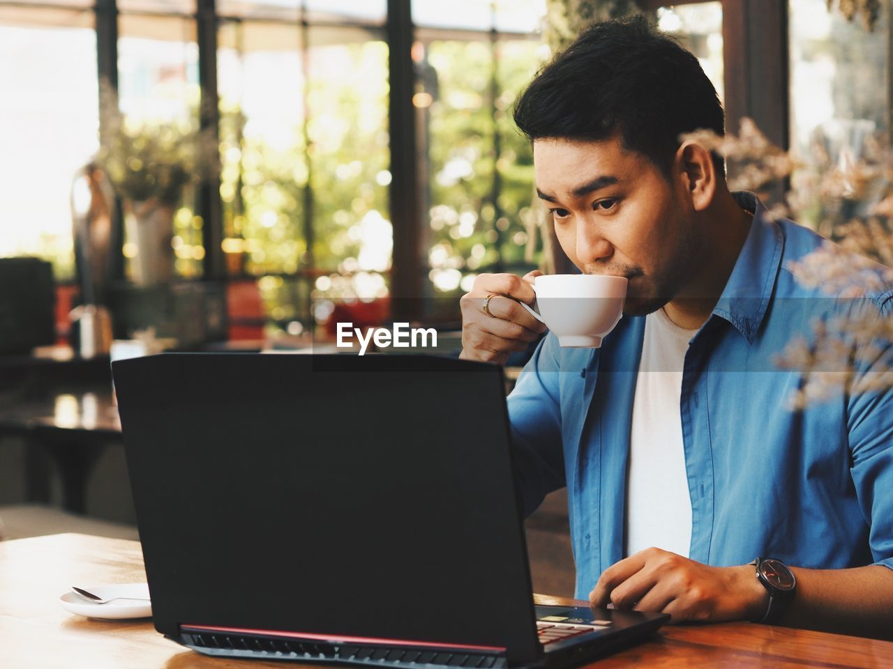Young man drinking coffee while using laptop from table
