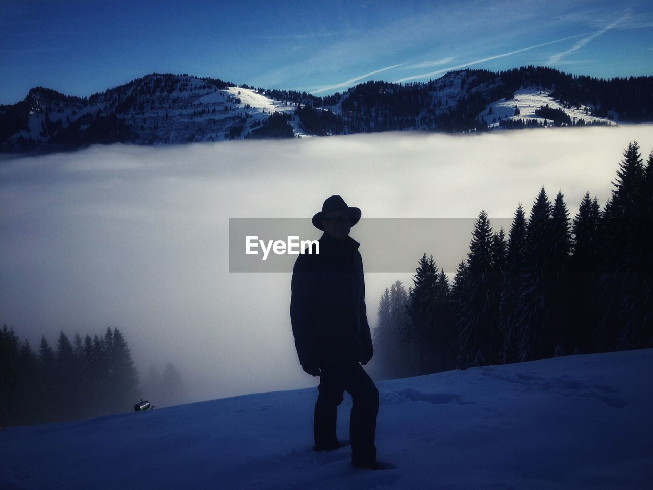 Silhouette man standing on snowcapped mountain against sky