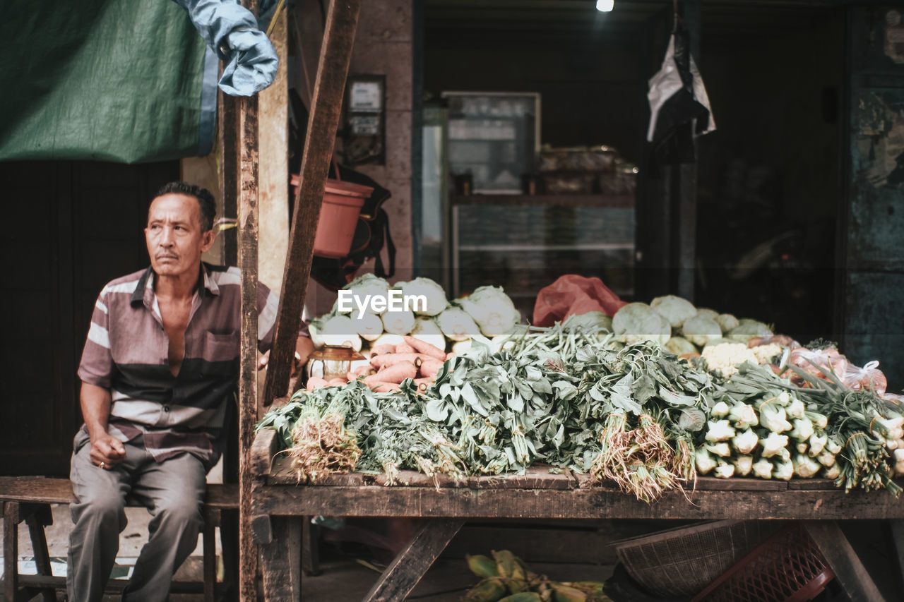 Portrait of man for sale at market stall