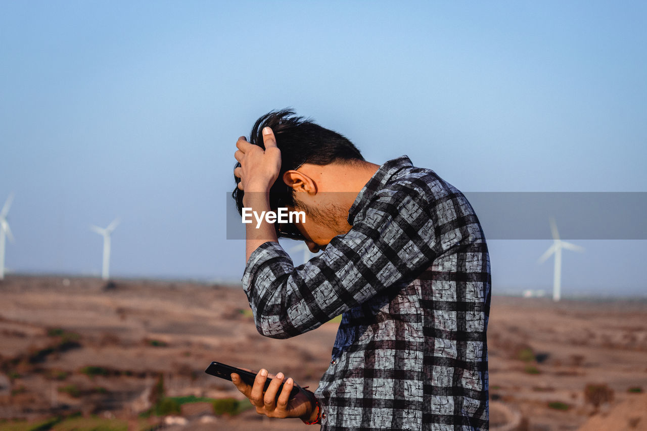 Young man using mobile phone against clear blue sky