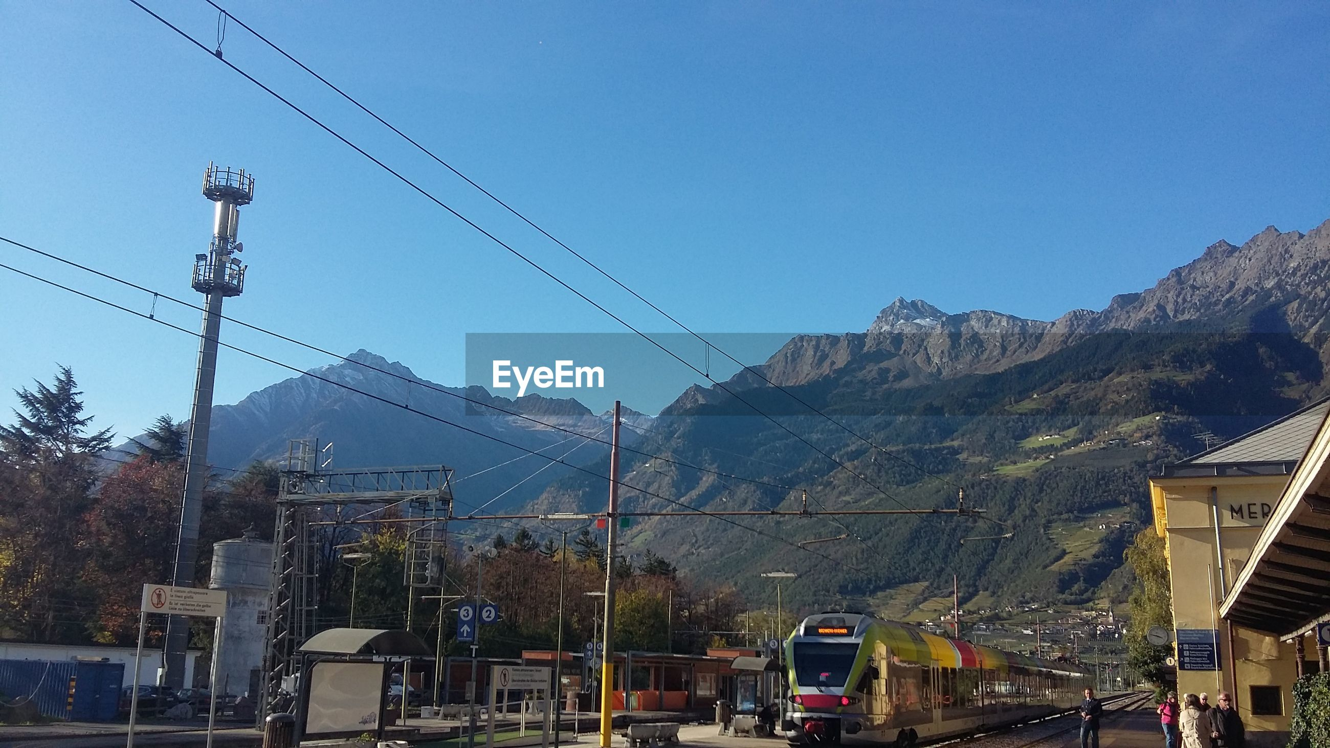 Overhead cable cars and mountains against clear blue sky