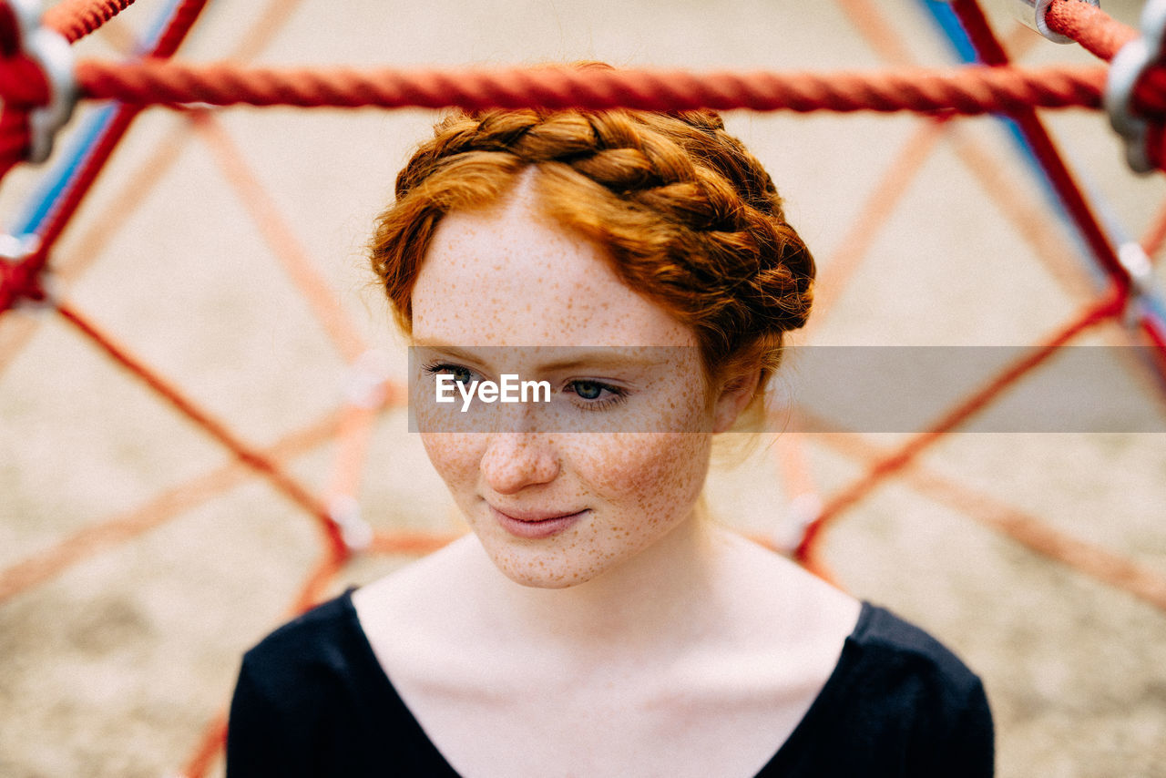 one person, redhead, focus on foreground, high angle view, portrait, looking at camera, day, headshot, real people, young adult, outdoors, young women, one young woman only, close-up, people