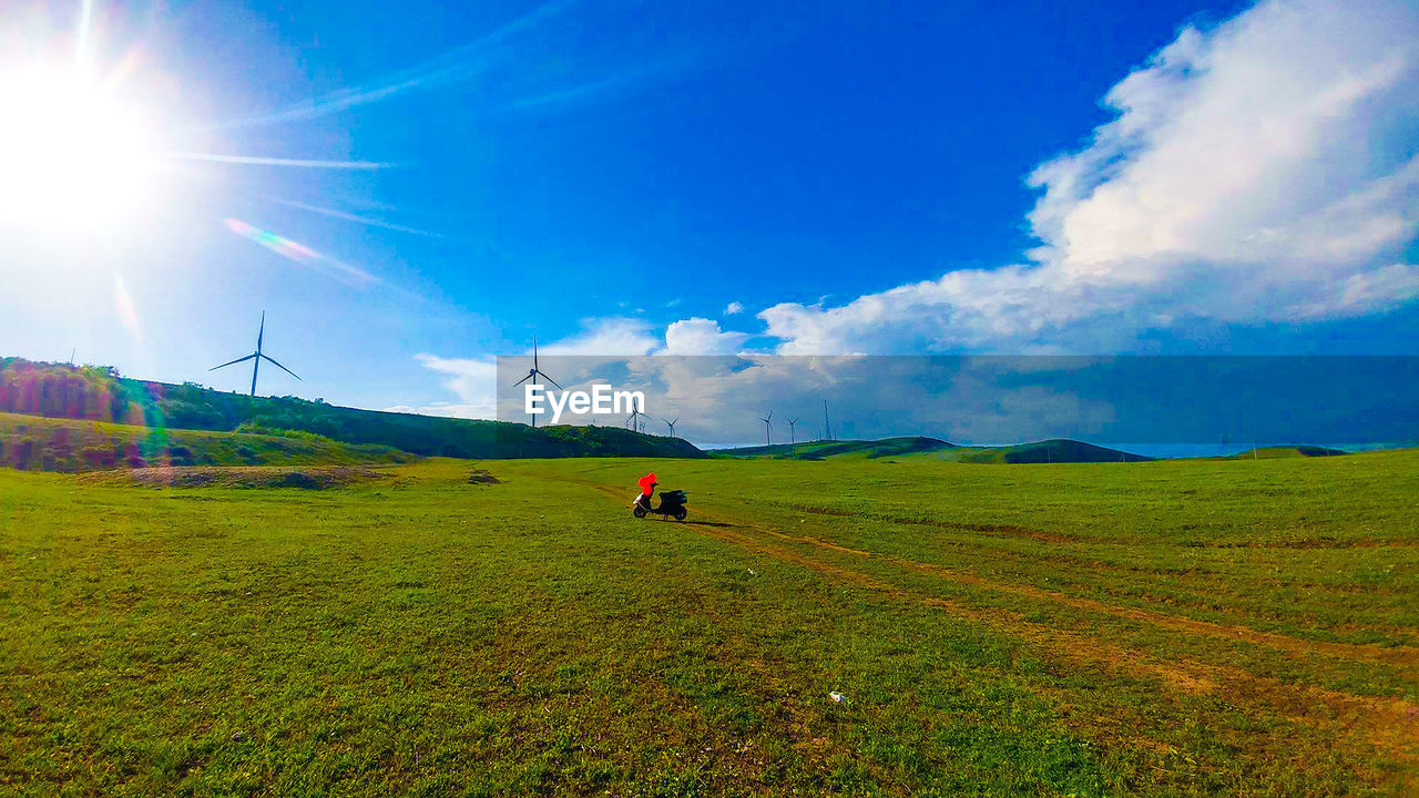 sky, beauty in nature, environment, scenics - nature, landscape, land, real people, nature, grass, tranquil scene, cloud - sky, day, sunlight, tranquility, field, green color, non-urban scene, lifestyles, blue, idyllic, lens flare, outdoors, sun, bright