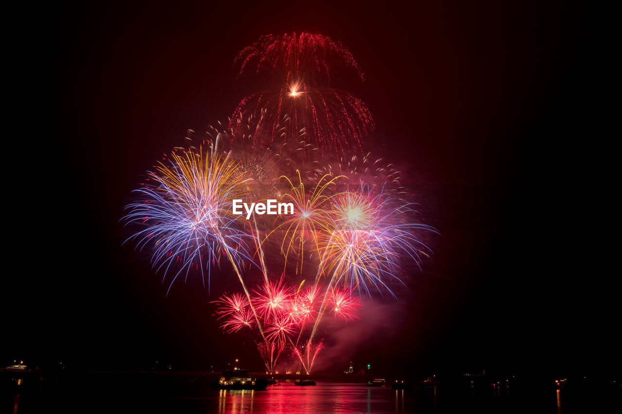 illuminated, night, firework, celebration, motion, event, firework display, arts culture and entertainment, exploding, sky, glowing, no people, long exposure, nature, architecture, light, water, firework - man made object, low angle view, outdoors, sparks