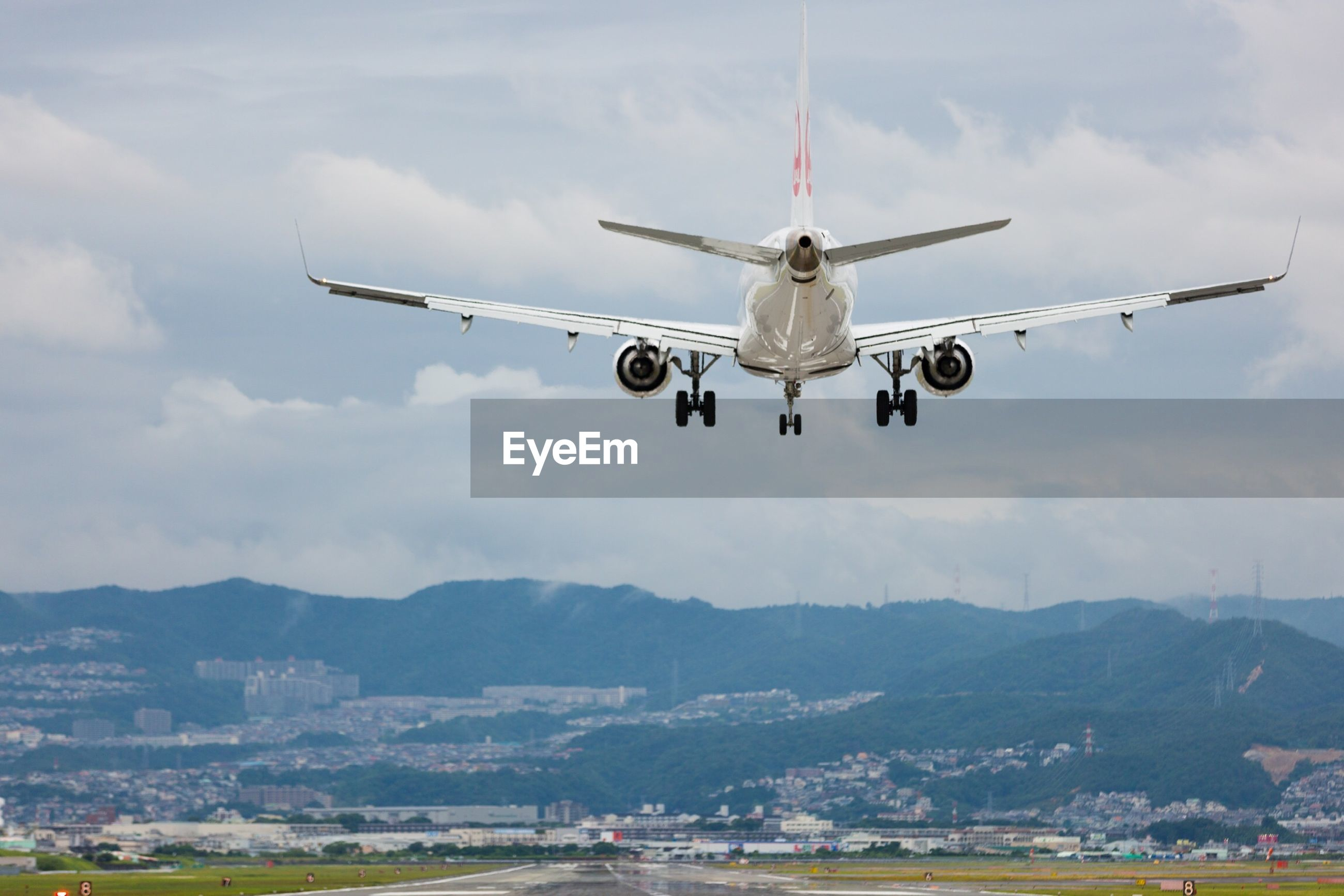 Airplane flying over runway against cloudy sky
