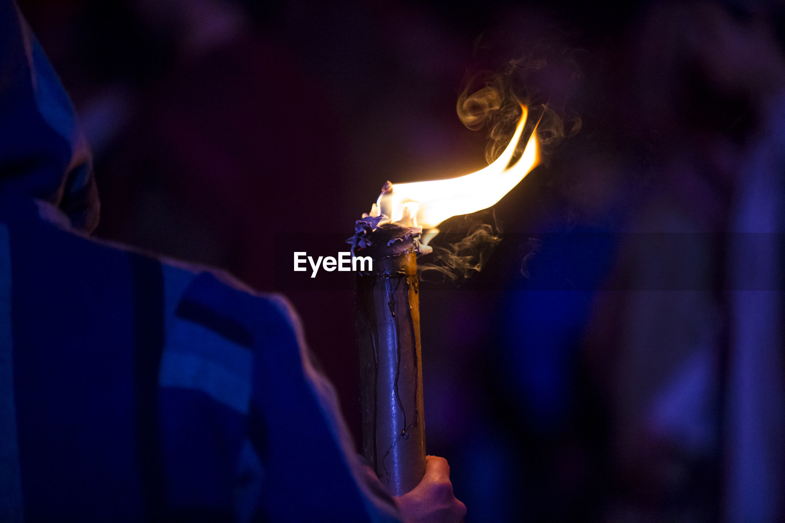 Cropped image of person holding flaming torch