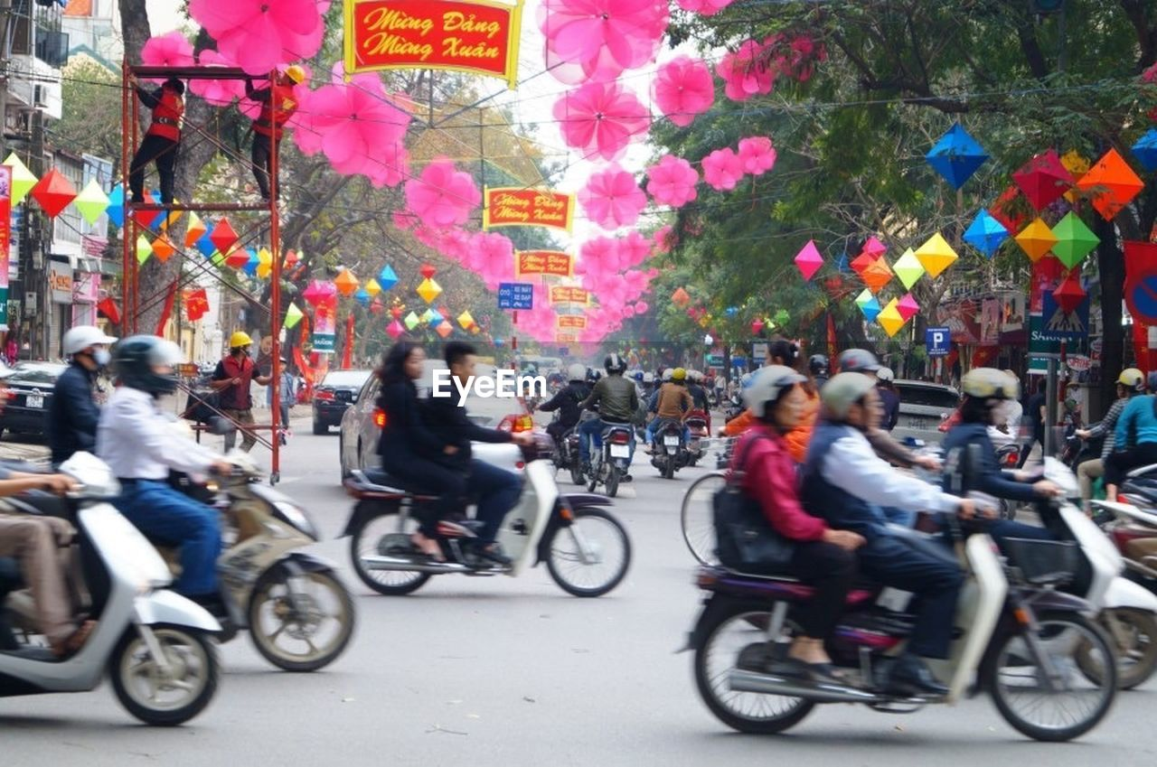 transportation, mode of transport, street, land vehicle, city, city street, bicycle, city life, motorcycle, multi colored, riding, outdoors, large group of people, day, travel, architecture, real people, road, men, motion, building exterior, people