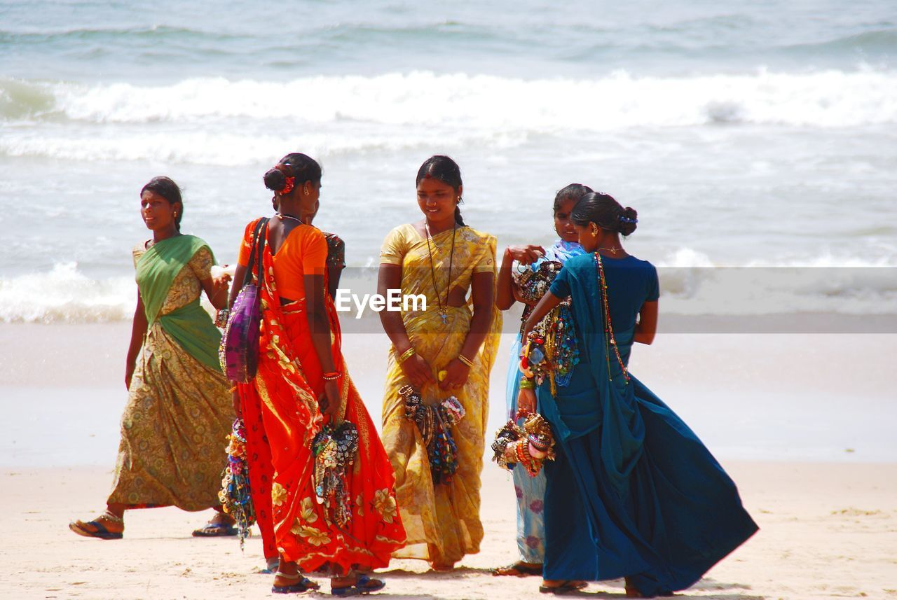 beach, traditional clothing, sea, full length, sand, real people, cultures, women, togetherness, water, standing, beauty in nature, day, life events, men, outdoors, wave, nature, bride, young women, young adult, sky