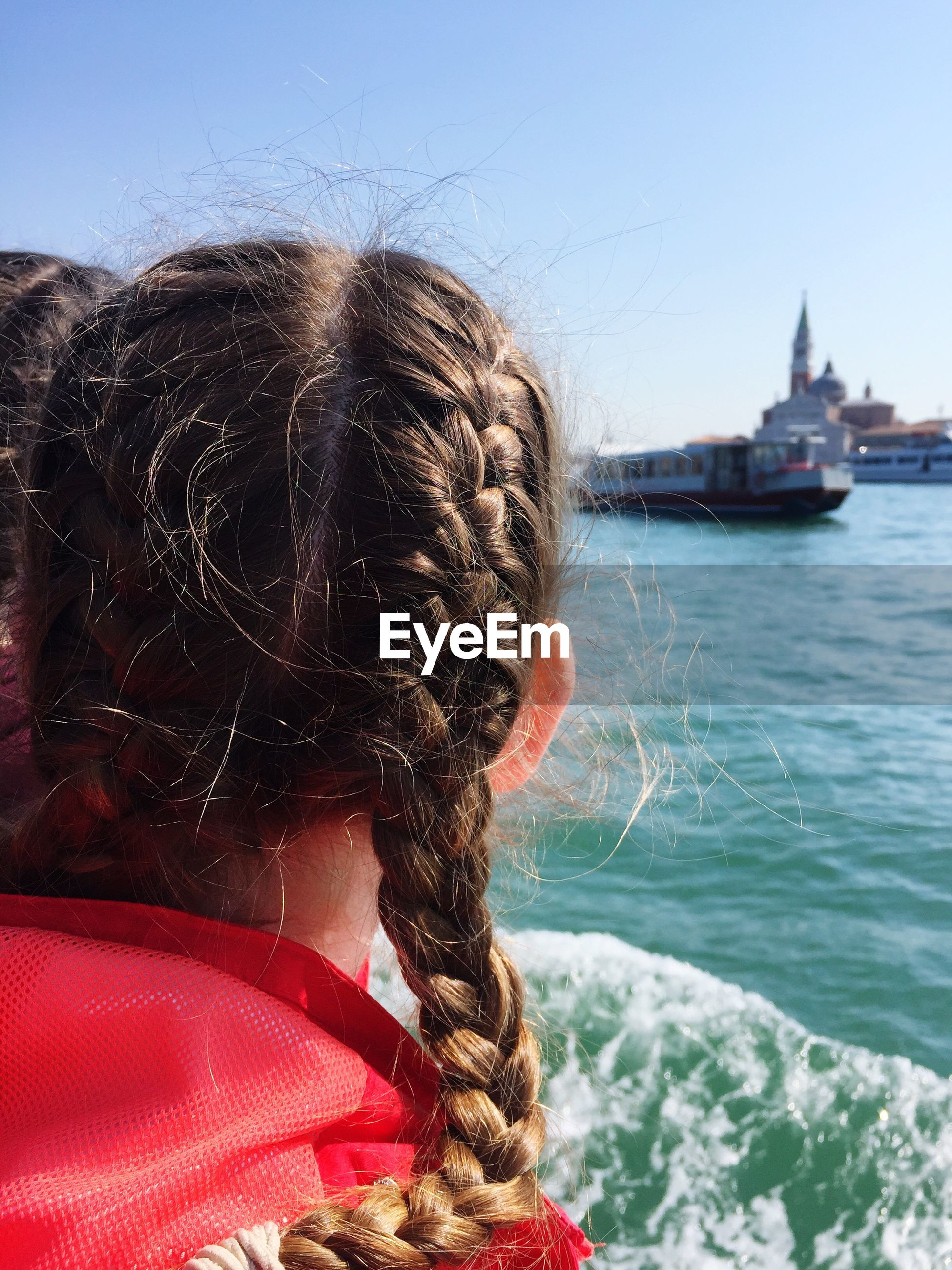 Rear view of woman with braided hair by grand canal against sky