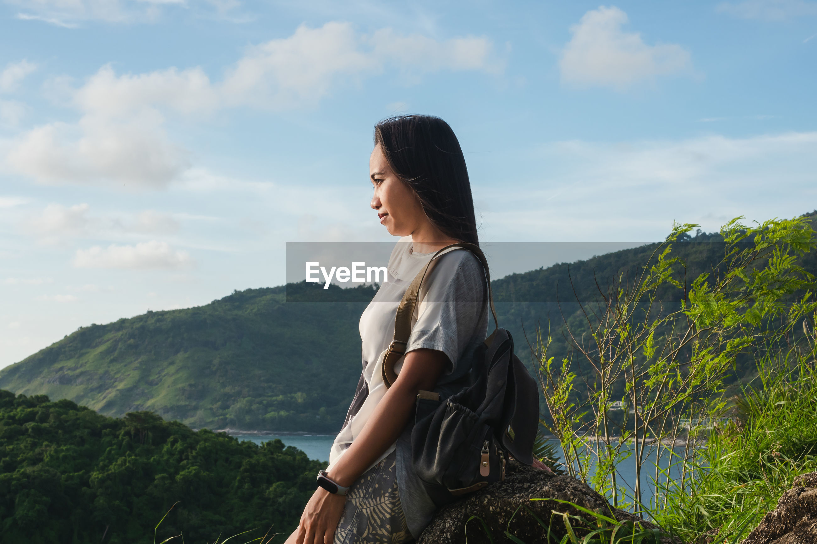 Side view of young woman looking at mountains against sky