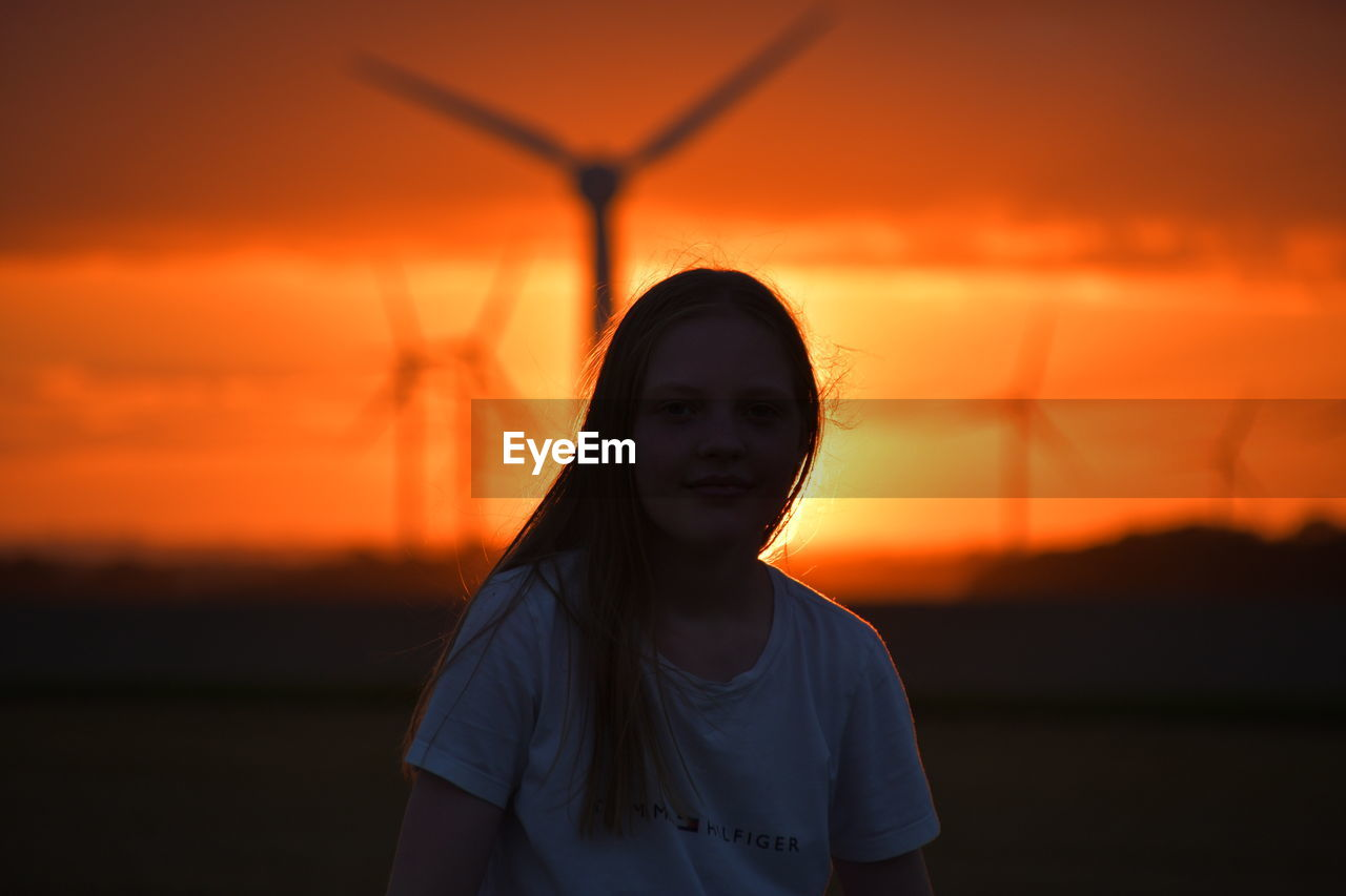 Girl and sunset over the holderness fields at rimswell east yorkshire uk wind turbine in background