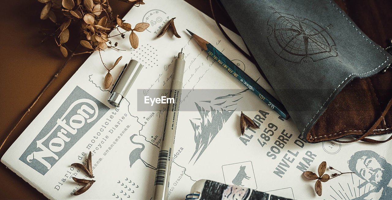 indoors, paper, no people, still life, high angle view, pen, table, large group of objects, creativity, art and craft, representation, publication, text, close-up, book, directly above, pencil, writing instrument, craft, human representation, personal accessory, leather